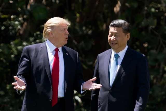 US President Donald Trump (L) and Chinese President Xi Jinping (R) walk together at the Mar-a-Lago estate in West Palm Beach, Florida, April 7, 2017. President Donald Trump entered a second day of talks with his Chinese counterpart Xi Jinping on Friday hoping to strike deals on trade and jobs after an overnight show of strength in Syria. / AFP PHOTO / JIM WATSON