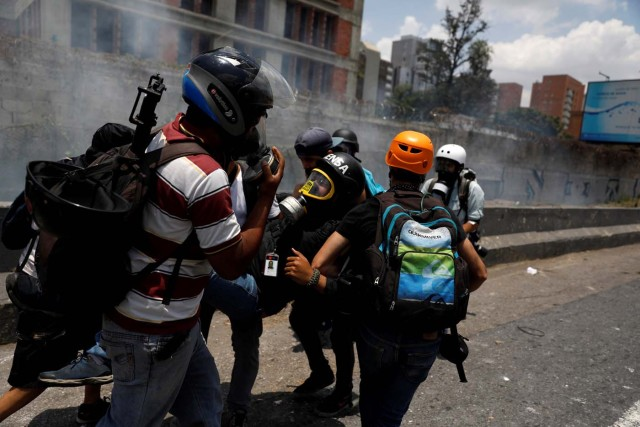 A member of the media is helped during a rally against Venezuela's President Nicolas Maduro's government in Caracas, Venezuela April 10, 2017. REUTERS/Carlos Garcia Rawlins