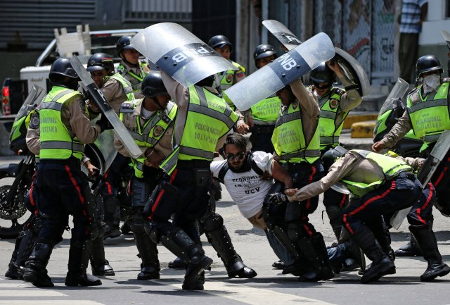 A demonstrator is arrested by riot police while rallying against Venezuela's President Nicolas Maduro's government in Caracas