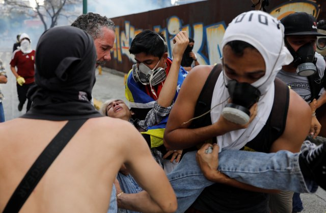 A injured demonstrator is helped by others during a rally against Venezuela's President Nicolas Maduro's government in Caracas, Venezuela April 10, 2017. REUTERS/Carlos Garcia Rawlins