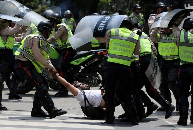 A demonstrator is arrested by riot police while rallying against Venezuela's President Nicolas Maduro's government in Caracas, Venezuela April 10, 2017. REUTERS/Carlos Garcia Rawlins