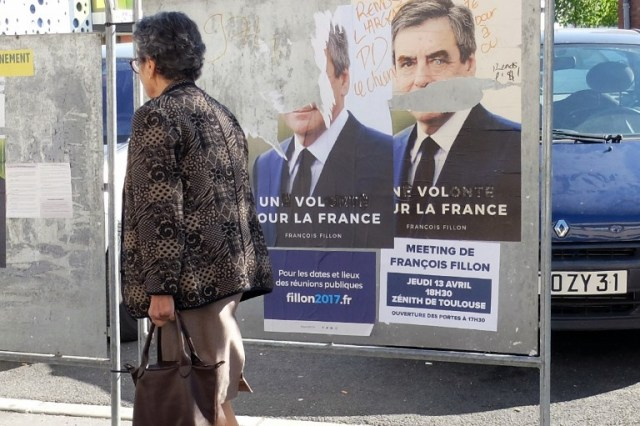 This picture taken in Toulouse on April 18, 2017, shows an electoral poster of French presidential election candidate for the right-wing Les Republicains (LR) party Francois Fillon defaced. / AFP PHOTO / PASCAL PAVANI