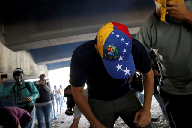 """Venezuelan opposition leader and Governor of Miranda state Capriles tries to catch his breath after being affected by tear gas while participating in the so-called """"mother of all marches"""" against Venezuela's President Nicolas Maduro in Caracas"""