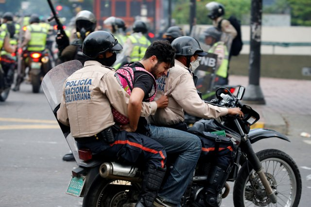 """A demonstrator is detained by riot police officers during the so called """"mother of all marches"""" against Venezuela's President Nicolas Maduro in Caracas, Venezuela, April 19, 2017. REUTERS/Carlos Garcia Rawlins"""