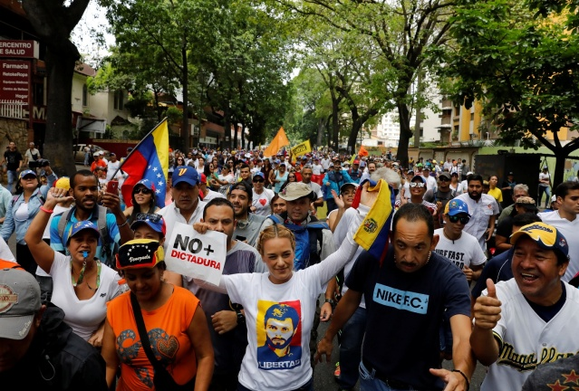 """Lilian Tintori (C), a wife of jailed opposition leader Leopoldo Lopez, rallies during the so-called """"mother of all marches"""" against Venezuela's President Nicolas Maduro carrying a sing that reads """"No more dictatorship"""" in Caracas, Venezuela April 19, 2017. REUTERS/Carlos Garcia Rawlins"""