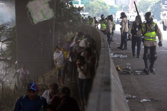 CAR232. CARACAS (VENEZUELA), 19/04/2017 - Un grupo de manifestantes camina a la orilla de una vía mientras miembros de la policía custodian durante una protesta en contra del Gobierno venezolano hoy, miércoles 19 de abril de 2017, en Caracas (Venezuela). Centenares de opositores en distintos puntos de caracas se enfrentaron hoy a los cuerpos de seguridad para mantenerse en las calles protestando, pese al uso de bombas lacrimógenas por parte de las fuerzas policiales para dispersar y bloquear el paso de las marchas. EFE/CRISTIAN HERNANDEZ