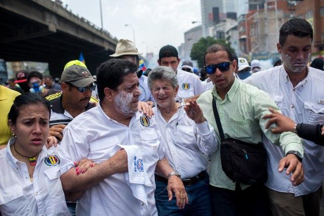 CAR006. CARACAS (VENEZUELA), 19/04/2017.- El expresidente del parlamento y líder opositor Henry Ramos Allup (c) reacciona a los gases lacrimógenos durante una manifestación opositora que intentaba llegar a la Defensoría del Pueblo hoy, miércoles 19 de abril de 2017, en Caracas (Venezuela.). La policía disolvió hoy con gases lacrimógenos una de las marchas opositoras en el centro de Caracas que pretendía llegar a la sede de la Defensoría del Pueblo, mientras que desde otra de las concentraciones antichavistas en esa zona de la ciudad se reportó una persona muerta. Venezuela es escenario el día de hoy de marchas a favor y en contra del Gobierno a las que cada uno de los bandos ha convocado para medir fuerzas en la calle. EFE/Manaure Quintero