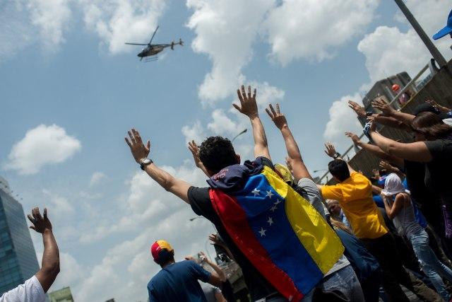 CAR006. CARACAS (VENEZUELA), 19/04/2017.- Un grupo de personas reacciona ante el paso de un helicóptero durante una manifestación opositora que intentaba llegar a la Defensoría del Pueblo hoy, miércoles 19 de abril de 2017, en Caracas (Venezuela.). La policía disolvió hoy con gases lacrimógenos una de las marchas opositoras en el centro de Caracas que pretendía llegar a la sede de la Defensoría del Pueblo, mientras que desde otra de las concentraciones antichavistas en esa zona de la ciudad se reportó una persona muerta. Venezuela es escenario el día de hoy de marchas a favor y en contra del Gobierno a las que cada uno de los bandos ha convocado para medir fuerzas en la calle. EFE/Manaure Quintero