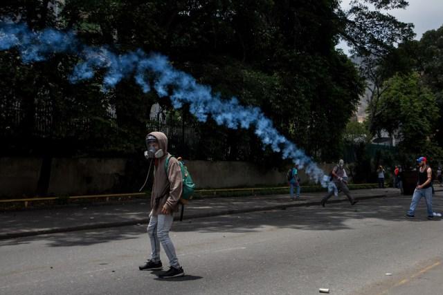 CAR007. CARACAS (VENEZUELA),19/04/2017 - Manifestantes se enfrentan con la policía durante una protesta en contra del Gobierno venezolano hoy, miércoles 19 de abril de 2017, en Caracas (Venezuela). El chavismo y la oposición se cruzaron hoy en las calles de Caracas con sendas marchas para medir el respaldo a favor y en contra del Gobierno de Nicolás Maduro en medio de la tensión política y una ola de protestas opositoras que han dejado al menos 5 muertos, y centenares de heridos y detenidos. EFE/MIGUEL GUTIERREZ