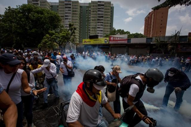 CAR012. CARACAS (VENEZUELA),19/04/2017 - Manifestantes se protegen de los gases lacrimógenos durante una protesta en contra del Gobierno venezolano hoy, miércoles 19 de abril de 2017, en Caracas (Venezuela). La policía disolvió hoy con gases lacrimógenos una de las marchas opositoras en el centro de Caracas que pretendía llegar a la sede de la Defensoría del Pueblo, mientras que desde otra de las concentraciones antichavistas en esa zona de la ciudad se reportó una persona muerta. EFE/MIGUEL GUTIERREZ