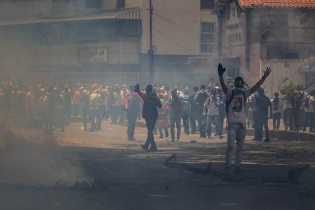 CAR0164. CARACAS (VENEZUELA),19/04/2017 - Manifestantes se enfrentan con la policía durante una protesta en contra del Gobierno venezolano hoy, miércoles 19 de abril de 2017, en Caracas (Venezuela). La policía disolvió hoy con gases lacrimógenos una de las marchas opositoras en el centro de Caracas que pretendía llegar a la sede de la Defensoría del Pueblo, mientras que desde otra de las concentraciones antichavistas en esa zona de la ciudad se reportó una persona muerta. EFE/MIGUEL GUTIERREZ