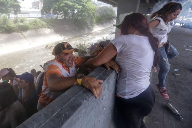 CAR233. CARACAS (VENEZUELA), 19/04/2017 - Una mujer ayuda a un hombre a subir de una pendiente a la orilla de una vía durante una protesta en contra del Gobierno venezolano hoy, miércoles 19 de abril de 2017, en Caracas (Venezuela). Centenares de opositores en distintos puntos de caracas se enfrentaron hoy a los cuerpos de seguridad para mantenerse en las calles protestando, pese al uso de bombas lacrimógenas por parte de las fuerzas policiales para dispersar y bloquear el paso de las marchas. EFE/CRISTIAN HERNANDEZ