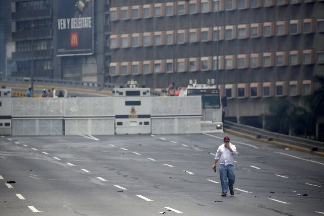 """Riot police take position behind a road blockade while clashing with demonstrators during the so-called """"mother of all marches"""" against Venezuela's President Nicolas Maduro in Caracas, Venezuela April 19, 2017. REUTERS/Marco Bello"""