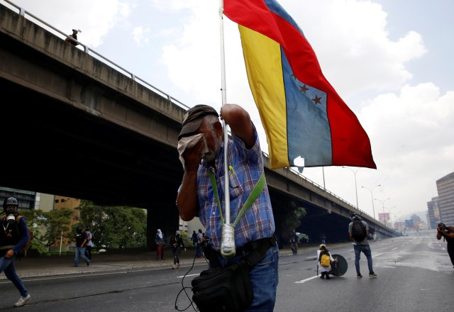 """A demonstrator carries Venezuela's flag while clashing with riot police during the so-called """"mother of all marches"""" against Venezuela's President Nicolas Maduro in Caracas, Venezuela April 19, 2017. REUTERS/Christian Veron"""