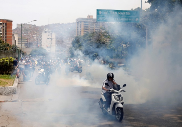 """Demonstrators clash with riot police during the so-called """"mother of all marches"""" against Venezuela's President Nicolas Maduro in Caracas, Venezuela April 19, 2017. REUTERS/Carlos Garcia Rawlins"""