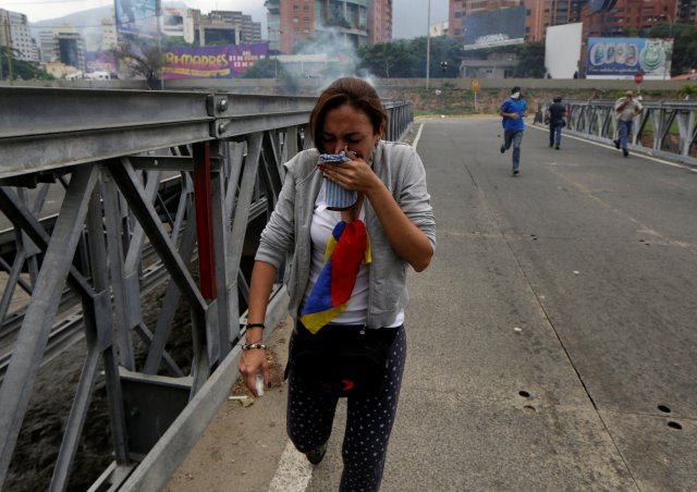 Opposition supporters run away from tear gas while rallying against Venezuela's President Nicolas Maduro in Caracas, Venezuela, April 20, 2017. REUTERS/Marco Bello