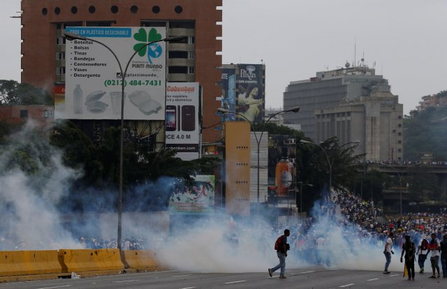 Demonstrators are seen amidst tear gas during clashes with police while rallying against Venezuela's President Nicolas Maduro in Caracas, Venezuela, April 20, 2017. REUTERS/Carlos Garcia Rawlins