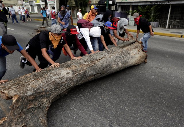 Demonstrators push a tree trunk to be used as barricade during clashes with police while rallying against Venezuela's President Nicolas Maduro in Caracas, Venezuela, April 20, 2017. REUTERS/Marco Bello