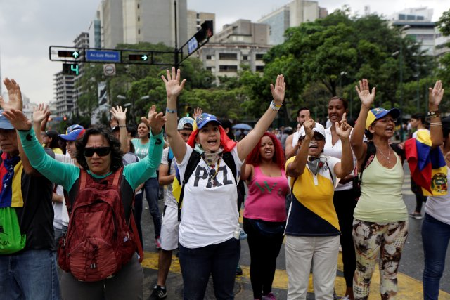 Demonstrators raise their arms during clashes with police while rallying against Venezuela's President Nicolas Maduro in Caracas, Venezuela, April 20, 2017. REUTERS/Marco Bello