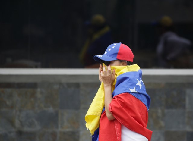 REFILE - CORRECTING BYLINEAn opposition supporter reacts to tear gas during clashes while rallying against Venezuela's President Nicolas Maduro in Caracas, Venezuela, April 20, 2017. REUTERS/Marco Bello