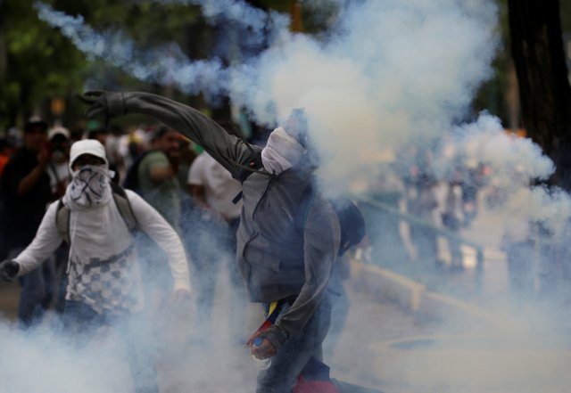 REFILE -  CORRECTING BYLINE A demonstrator throws a tear gas canister back to police during clashes while rallying against Venezuela's President Nicolas Maduro in Caracas, Venezuela, April 20, 2017. REUTERS/Marco Bello