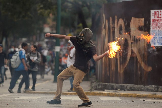 A demonstrator throws a molotov cocktail during clashes with riot police while rallying against Venezuela's President Nicolas Maduro in Caracas, Venezuela, April 20, 2017. REUTERS/Christian Veron