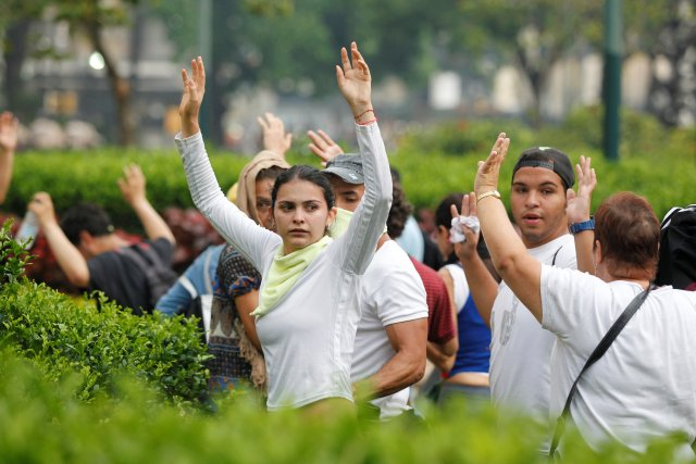Demonstrators raise their arms during clashes with police while rallying against Venezuela's President Nicolas Maduro in Caracas, Venezuela, April 20, 2017. REUTERS/Christian Veron