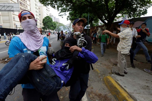 An injured demonstrator is helped during clashes with riot police while rallying against Venezuela's President Nicolas Maduro in Caracas, Venezuela, April 20, 2017. REUTERS/Marco Bello