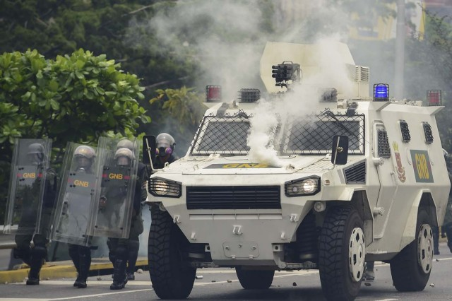 Riot police agents next to an armoured vehicle move forward along a blocked street, during clashes within a protest against Venezuelan President Nicolas Maduro, in Caracas on May 3, 2017. Venezuela's angry opposition rallied Wednesday vowing huge street protests against President Nicolas Maduro's plan to rewrite the constitution and accusing him of dodging elections to cling to power despite deadly unrest. / AFP PHOTO / RONALDO SCHEMIDT