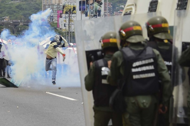 Riot police agents clash with demonstrators during a protest against Venezuelan President Nicolas Maduro, in Caracas on May 3, 2017. Venezuela's angry opposition rallied Wednesday vowing huge street protests against President Nicolas Maduro's plan to rewrite the constitution and accusing him of dodging elections to cling to power despite deadly unrest. / AFP PHOTO / RONALDO SCHEMIDT