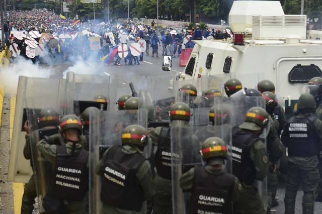 Riot police and demonstrators clash during a protest against Venezuelan President Nicolas Maduro, in Caracas on May 3, 2017. Venezuela's angry opposition rallied Wednesday vowing huge street protests against President Nicolas Maduro's plan to rewrite the constitution and accusing him of dodging elections to cling to power despite deadly unrest. / AFP PHOTO / RONALDO SCHEMIDT