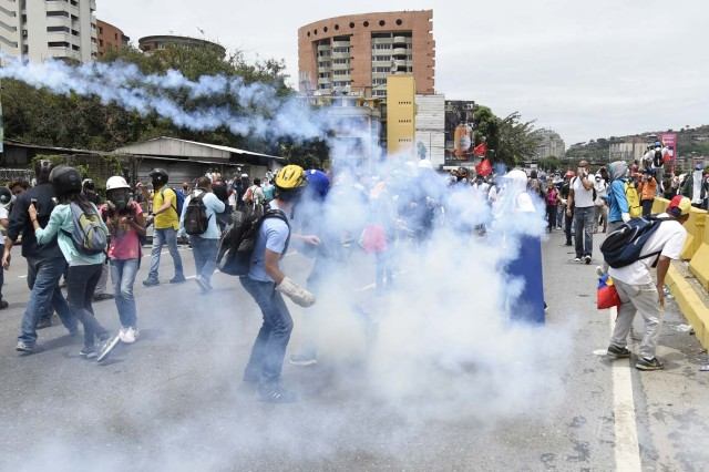 Demonstrators march amid tear gas during a protest against Venezuelan President Nicolas Maduro, in Caracas on May 3, 2017. Venezuela's angry opposition rallied Wednesday vowing huge street protests against President Nicolas Maduro's plan to rewrite the constitution and accusing him of dodging elections to cling to power despite deadly unrest. / AFP PHOTO / JUAN BARRETO