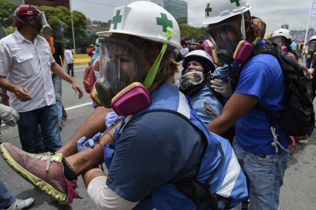 A demonstrator is attended by medical staff during a protest against Venezuelan President Nicolas Maduro, in Caracas on May 3, 2017. Venezuela's angry opposition rallied Wednesday vowing huge street protests against President Nicolas Maduro's plan to rewrite the constitution and accusing him of dodging elections to cling to power despite deadly unrest. / AFP PHOTO / JUAN BARRETO
