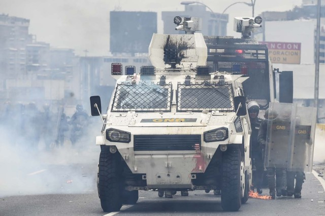 Riot police agents next to an armoured vehicle move forward along a blocked street, during clashes within a protest against Venezuelan President Nicolas Maduro, in Caracas on May 3, 2017. Venezuela's angry opposition rallied Wednesday vowing huge street protests against President Nicolas Maduro's plan to rewrite the constitution and accusing him of dodging elections to cling to power despite deadly unrest. / AFP PHOTO / JUAN BARRETO