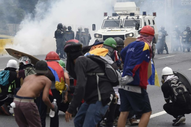 Demonstrators clash with riot police during a protest against Venezuelan President Nicolas Maduro, in Caracas on May 3, 2017. Venezuela's angry opposition rallied Wednesday vowing huge street protests against President Nicolas Maduro's plan to rewrite the constitution and accusing him of dodging elections to cling to power despite deadly unrest. / AFP PHOTO / JUAN BARRETO