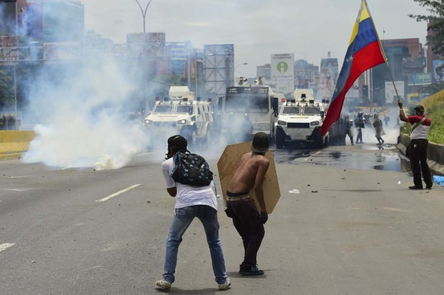 Demonstrators clash with riot police during a protest against Venezuelan President Nicolas Maduro, in Caracas on May 3, 2017. Venezuela's angry opposition rallied Wednesday vowing huge street protests against President Nicolas Maduro's plan to rewrite the constitution and accusing him of dodging elections to cling to power despite deadly unrest. / AFP PHOTO / RONALDO SCHEMIDT