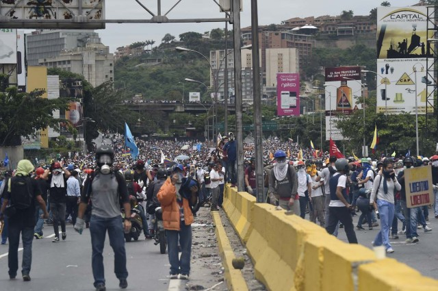 Demonstrators march along a major highway of Caracas during a protest against Venezuelan President Nicolas Maduro, on May 3, 2017. Venezuela's angry opposition rallied Wednesday vowing huge street protests against President Nicolas Maduro's plan to rewrite the constitution and accusing him of dodging elections to cling to power despite deadly unrest. / AFP PHOTO / JUAN BARRETO