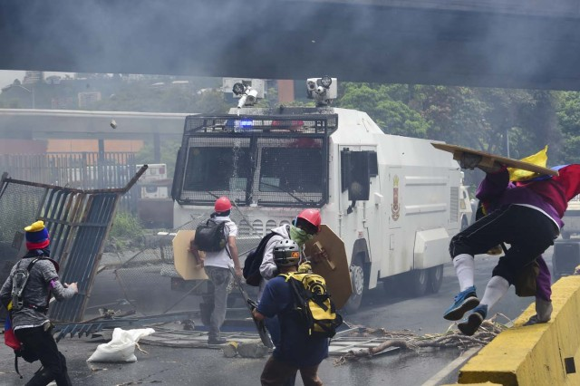 Demonstrators confront a riot police armoured vehicle during clashes within a protest against Venezuelan President Nicolas Maduro, on May 3, 2017. Venezuela's angry opposition rallied Wednesday vowing huge street protests against President Nicolas Maduro's plan to rewrite the constitution and accusing him of dodging elections to cling to power despite deadly unrest. / AFP PHOTO / RONALDO SCHEMIDT