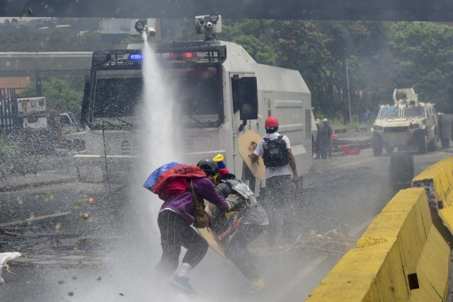 Demonstrators are sprayed by a riot police water cannon during clashes within a protest against Venezuelan President Nicolas Maduro, on May 3, 2017. Venezuela's angry opposition rallied Wednesday vowing huge street protests against President Nicolas Maduro's plan to rewrite the constitution and accusing him of dodging elections to cling to power despite deadly unrest. / AFP PHOTO / RONALDO SCHEMIDT