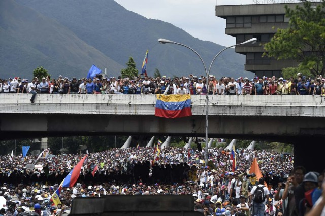 Demonstrators clash with riot police as they march along a major highway of Caracas during a protest against Venezuelan President Nicolas Maduro, on May 3, 2017. Venezuela's angry opposition rallied Wednesday vowing huge street protests against President Nicolas Maduro's plan to rewrite the constitution and accusing him of dodging elections to cling to power despite deadly unrest. / AFP PHOTO / JUAN BARRETO