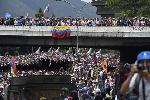 Opposition activists march during a protest against Venezuelan President Nicolas Maduro, in Caracas on May 3, 2017. Venezuela's angry opposition rallied Wednesday vowing huge street protests against President Nicolas Maduro's plan to rewrite the constitution and accusing him of dodging elections to cling to power despite deadly unrest. / AFP PHOTO / JUAN BARRETO