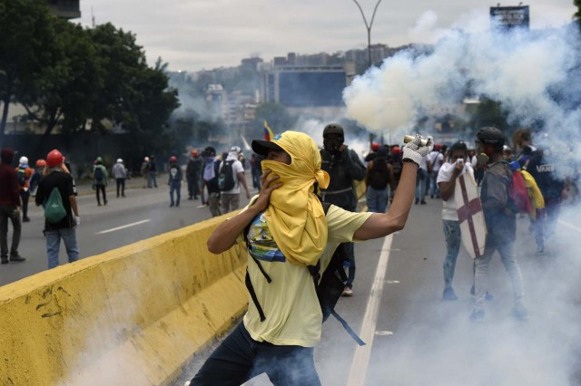 A demonstrator throws back tear gas to the police, during clashes within a protest against Venezuelan President Nicolas Maduro, in Caracas on May 3, 2017. Venezuela's angry opposition rallied Wednesday vowing huge street protests against President Nicolas Maduro's plan to rewrite the constitution and accusing him of dodging elections to cling to power despite deadly unrest. / AFP PHOTO / JUAN BARRETO