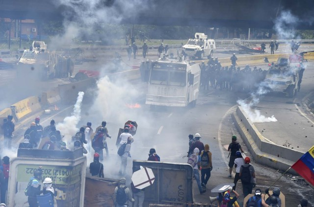 Opposition activists clash with riot police during a protest against Venezuelan President Nicolas Maduro, in Caracas on May 3, 2017. Venezuela's angry opposition rallied Wednesday vowing huge street protests against President Nicolas Maduro's plan to rewrite the constitution and accusing him of dodging elections to cling to power despite deadly unrest. / AFP PHOTO / JUAN BARRETO