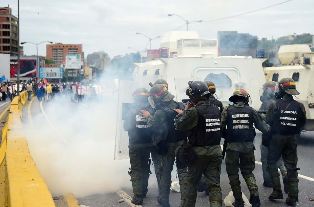 Opposition activists clash with riot police during a protest against Venezuelan President Nicolas Maduro, in Caracas on May 3, 2017. Venezuela's angry opposition rallied Wednesday vowing huge street protests against President Nicolas Maduro's plan to rewrite the constitution and accusing him of dodging elections to cling to power despite deadly unrest. / AFP PHOTO / RONALDO SCHEMIDT