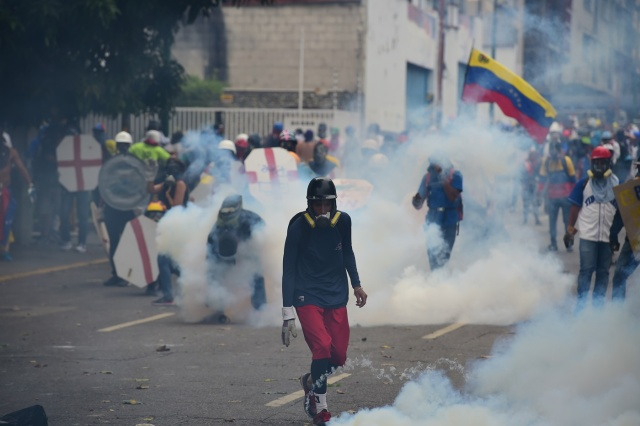 Engulfed in a cloud of tear gas shot by riot police, opposition demonstrators take cover behind makeshift shields during a protest against Venezuelan President Nicolas Maduro, in Caracas on May 3, 2017. Venezuela's angry opposition rallied Wednesday vowing huge street protests against President Nicolas Maduro's plan to rewrite the constitution and accusing him of dodging elections to cling to power despite deadly unrest. / AFP PHOTO / RONALDO SCHEMIDT