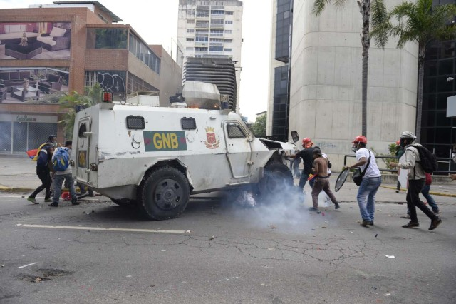 A Venezuelan National Guard riot control vehicle runs over an opposition demonstrator during a protest against Venezuelan President Nicolas Maduro, in Caracas on May 3, 2017. Venezuela's angry opposition rallied Wednesday vowing huge street protests against President Nicolas Maduro's plan to rewrite the constitution and accusing him of dodging elections to cling to power despite deadly unrest. / AFP PHOTO / FEDERICO PARRA / GRAPHIC CONTENT