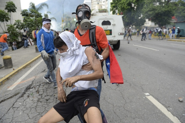 An opposition demonstrator ran over by a National Guard control vehicle is dragged away by a fellow demonstrator during a protest against Venezuelan President Nicolas Maduro, in Caracas on May 3, 2017. Venezuela's angry opposition rallied Wednesday vowing huge street protests against President Nicolas Maduro's plan to rewrite the constitution and accusing him of dodging elections to cling to power despite deadly unrest. / AFP PHOTO / FEDERICO PARRA