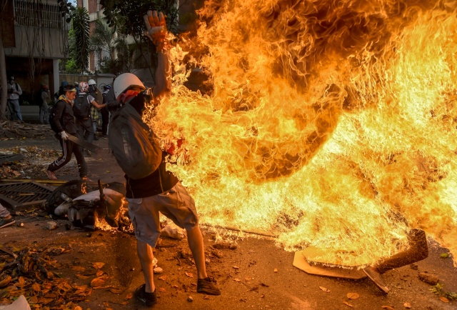 A man tries to help a fellow demonstrator who catched fire, after the gas tank of a police motorbike exploded, during clashes in a protest against Venezuelan President Nicolas Maduro, in Caracas on May 3, 2017. Venezuela's angry opposition rallied Wednesday vowing huge street protests against President Nicolas Maduro's plan to rewrite the constitution and accusing him of dodging elections to cling to power despite deadly unrest. / AFP PHOTO / JUAN BARRETO