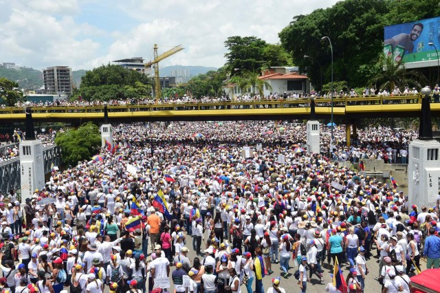 Venezuelan opposition activists take part in a women's march aimed to keep pressure on President Nicolas Maduro, whose authority is being increasingly challenged by protests and deadly unrest, in Caracas on May 6, 2017. The death toll since April, when the protests intensified after Maduro's administration and the courts stepped up efforts to undermine the opposition, is at least 36 according to prosecutors. / AFP PHOTO / RONALDO SCHEMIDT