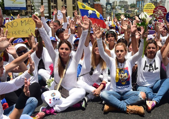 The wife of imprisoned opposition leader Leopoldo Lopez, Lilian Tintori (2nd R), takes part in a women's march aimed to keep pressure on President Nicolas Maduro, whose authority is being increasingly challenged by protests and deadly unrest, in Caracas on May 6, 2017. The death toll since April, when the protests intensified after Maduro's administration and the courts stepped up efforts to undermine the opposition, is at least 36 according to prosecutors. / AFP PHOTO / RONALDO SCHEMIDT